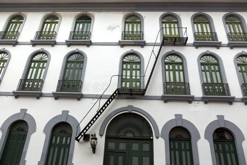 与白色门面的修造的外部和与绿色酒吧的绿色Windows在Casco Viejo奥尔德敦巴拿马市住宅区  免版税库存图片