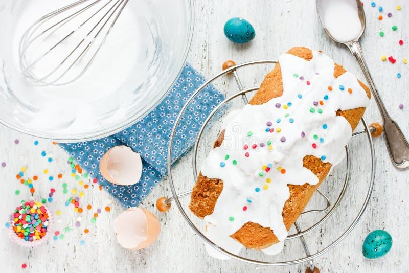 与白色结冰和五颜六色洒的复活节蛋糕在白色 图库摄影