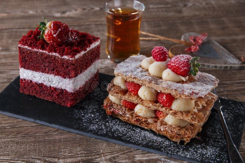 与白色结霜的Mille feuille点心甜切片红色天鹅绒蛋糕装饰用草莓 免版税库存照片