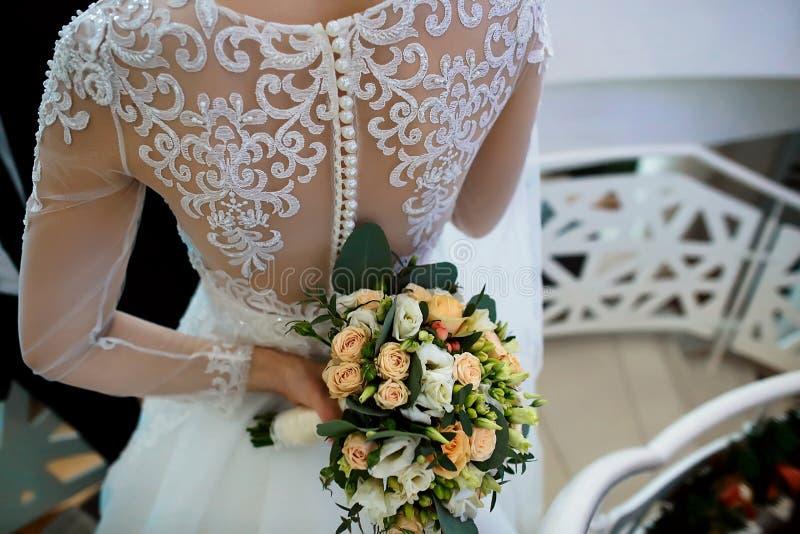 与白花和绿色的美丽的婚礼花束在新娘和新郎的手离开在礼服与鞋带 免版税图库摄影