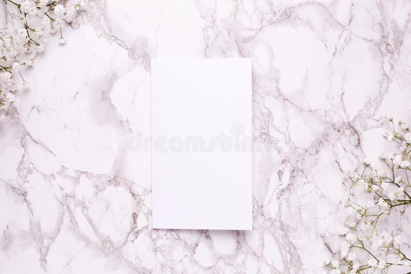 与白花的空的卡片在大理石台式视图和平的被放置的样式 免版税库存照片