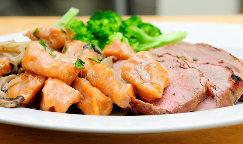 与白薯尼奥基的烤猪里脊肉 库存图片