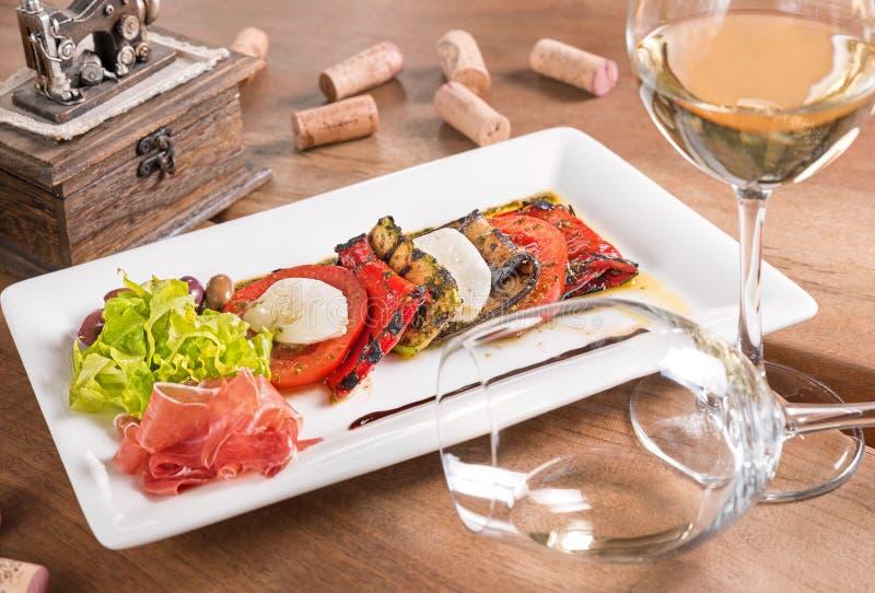 与白酒的开胃小菜在一块白色板材服务 免版税库存照片