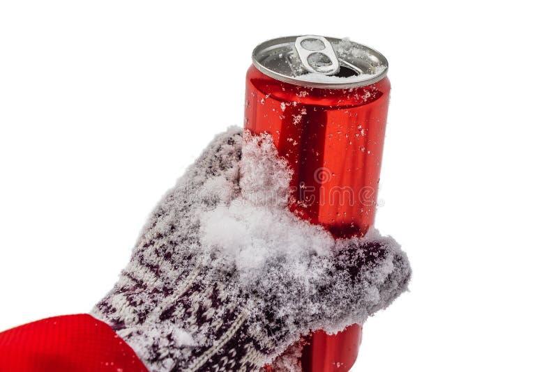 与白雪的被打开的红色锡罐与凉快的冷的汽水的钥匙在手套的一只手上 库存照片