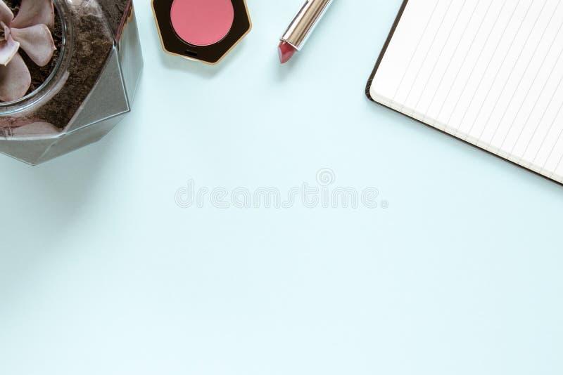 与白页的笔记,唇膏,脸红和在平的位置的花 r 库存图片