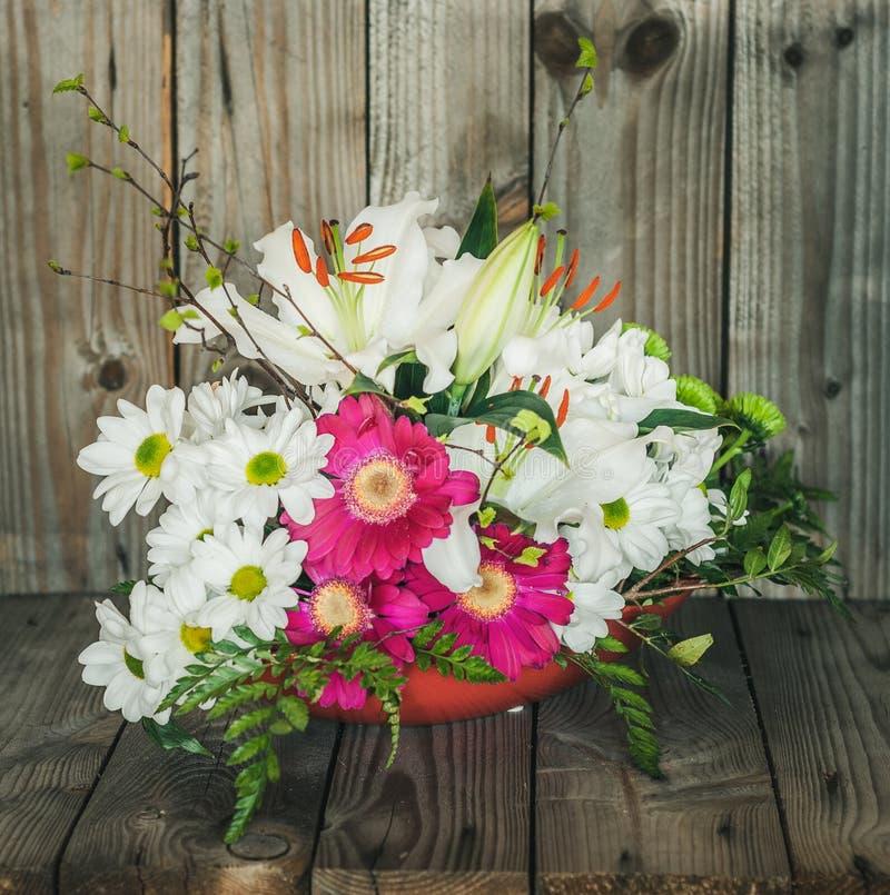 与百合和白色延命菊雏菊的艺术性的插花 免版税库存图片