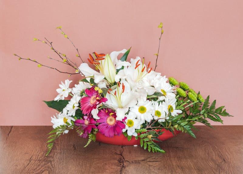 与百合和白色延命菊雏菊的艺术性的插花 库存照片