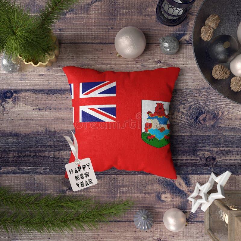 与百慕大旗子的新年快乐标记在枕头 在木桌上的圣诞装饰概念与可爱的对象 免版税库存图片