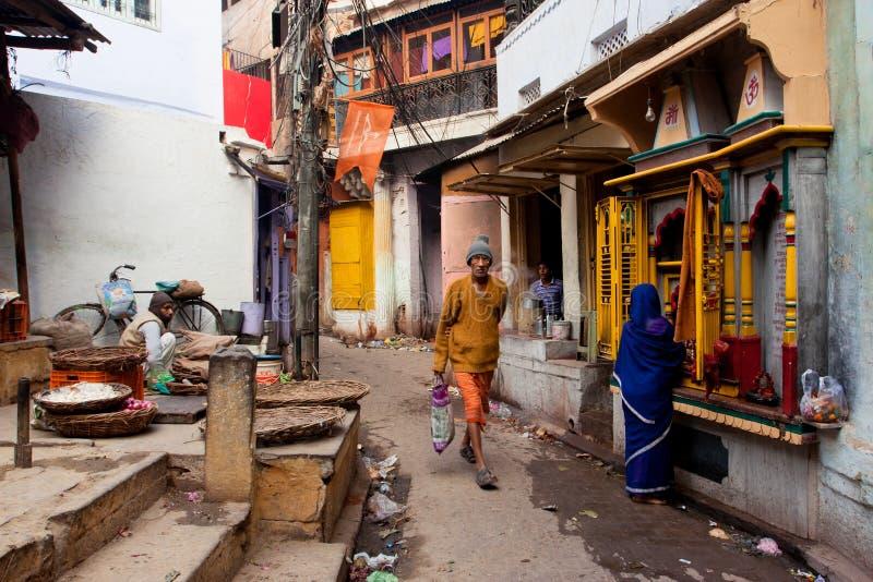 与的传统街道生活卖主、一名祈祷的妇女和路人人 免版税库存照片
