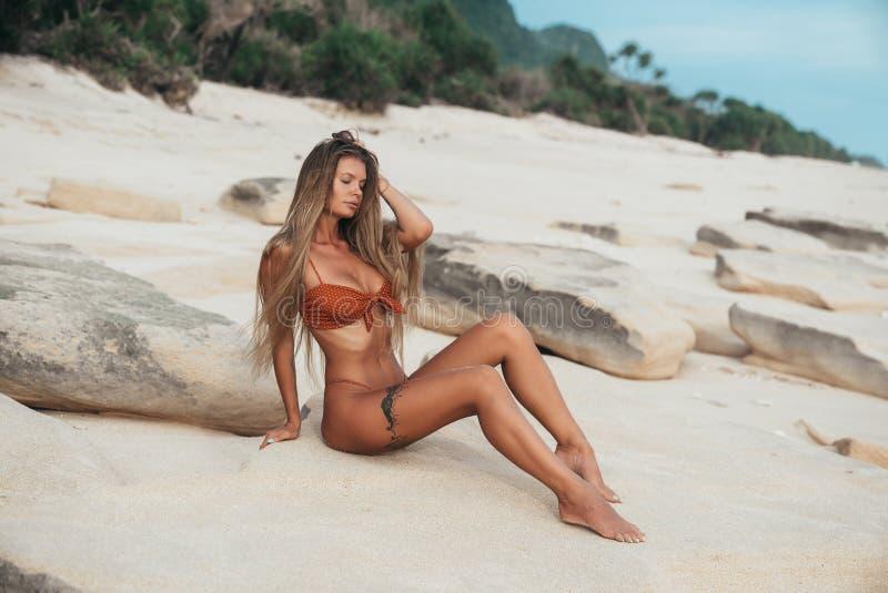 与的典雅的被晒黑的模型大美丽的乳房和苗条腿在沙子的泳装在 腿和手  图库摄影