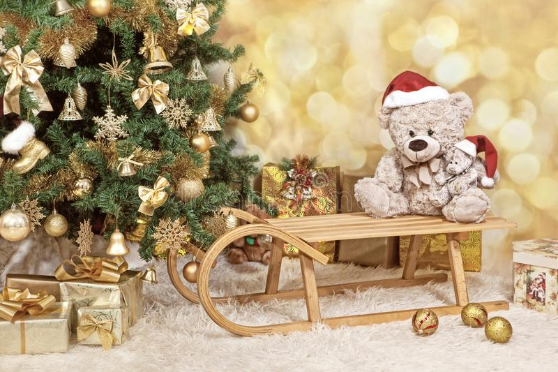 与的圣诞树金黄装饰品,玩具熊,爬犁和礼物 葡萄酒,乌贼属颜色 免版税库存照片