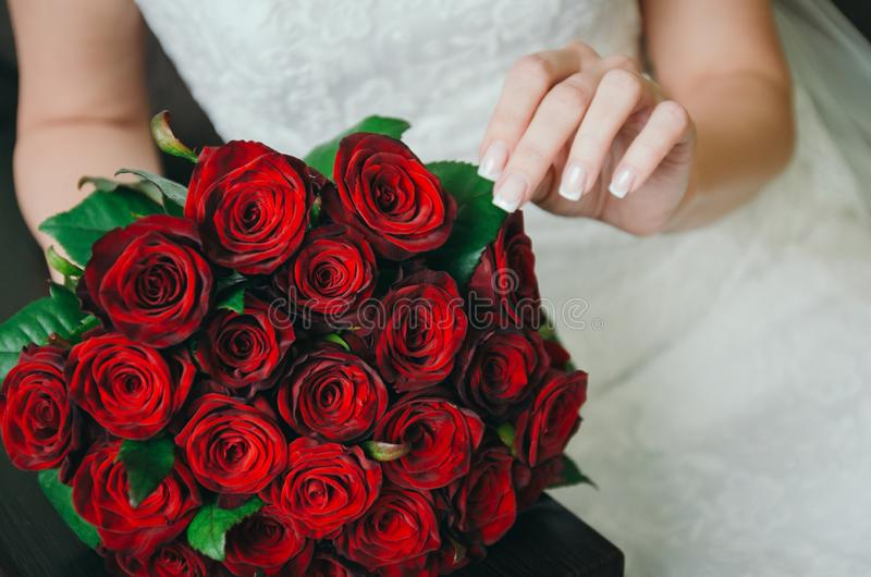 与的特写镜头新娘和新郎手和花束 新娘,拿着一婚姻的花束 婚姻的金戒指 新娘婚礼 免版税库存图片