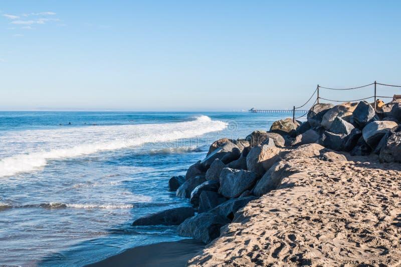与皇家海滩渔码头的岩石风景在背景中 免版税库存照片