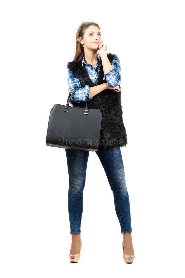 与皮包的年轻沉思查寻时装模特儿和的太阳镜 免版税库存照片