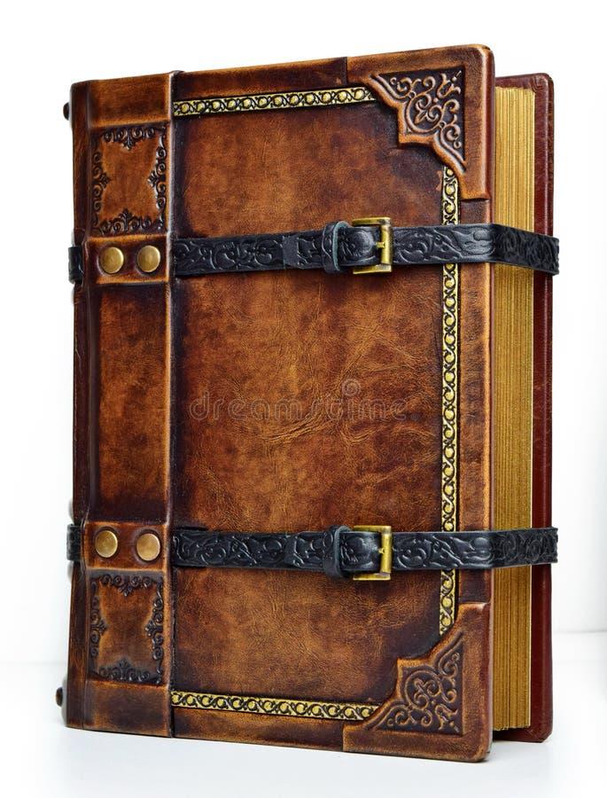 与皮带和被镀金的纸的边缘-从右边的看法的年迈的皮革书 免版税库存图片