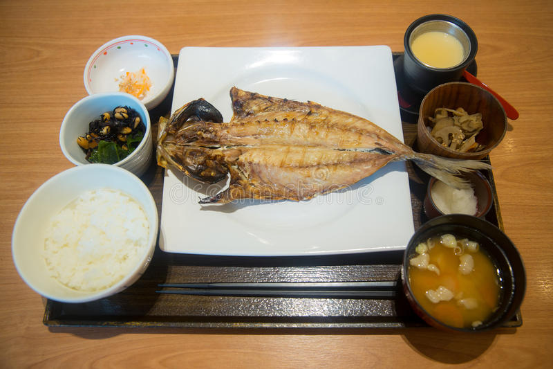 与皮肤、柠檬切片、叉子、钳子和刀子的新鲜的三文鱼在木砧板 图库摄影