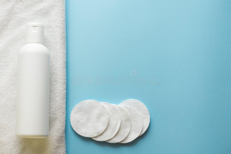 与皮肤护理化妆水的平的被放置的构成和在蓝色背景,拷贝空间的化装棉 免版税图库摄影