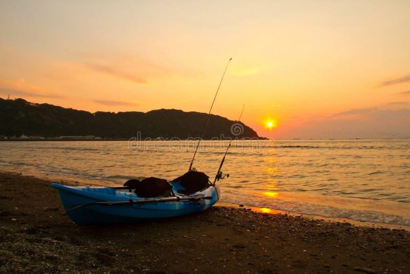 与皮船渔的海滩日落 免版税库存照片