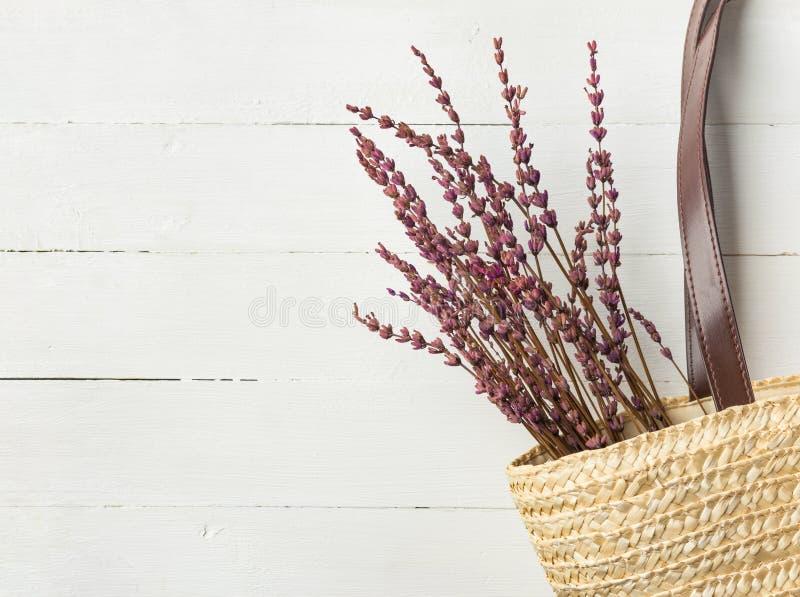与皮革把柄淡紫色花花束的秸杆手织的海滩书包在白色板条木头背景 普罗旺斯样式 免版税库存图片