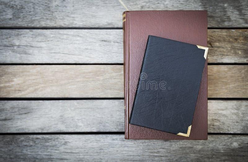 与皮革盖子的旧书在葡萄酒木地板背景 图库摄影