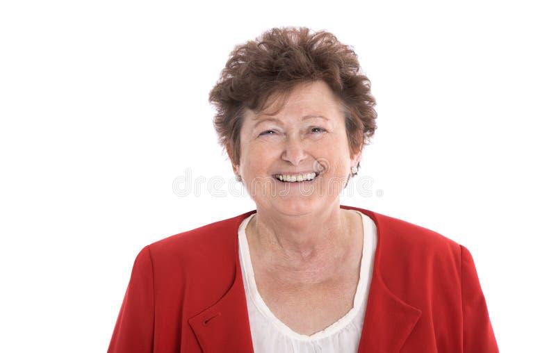 与皱痕和红色夹克的愉快的被隔绝的资深妇女面孔 免版税库存照片
