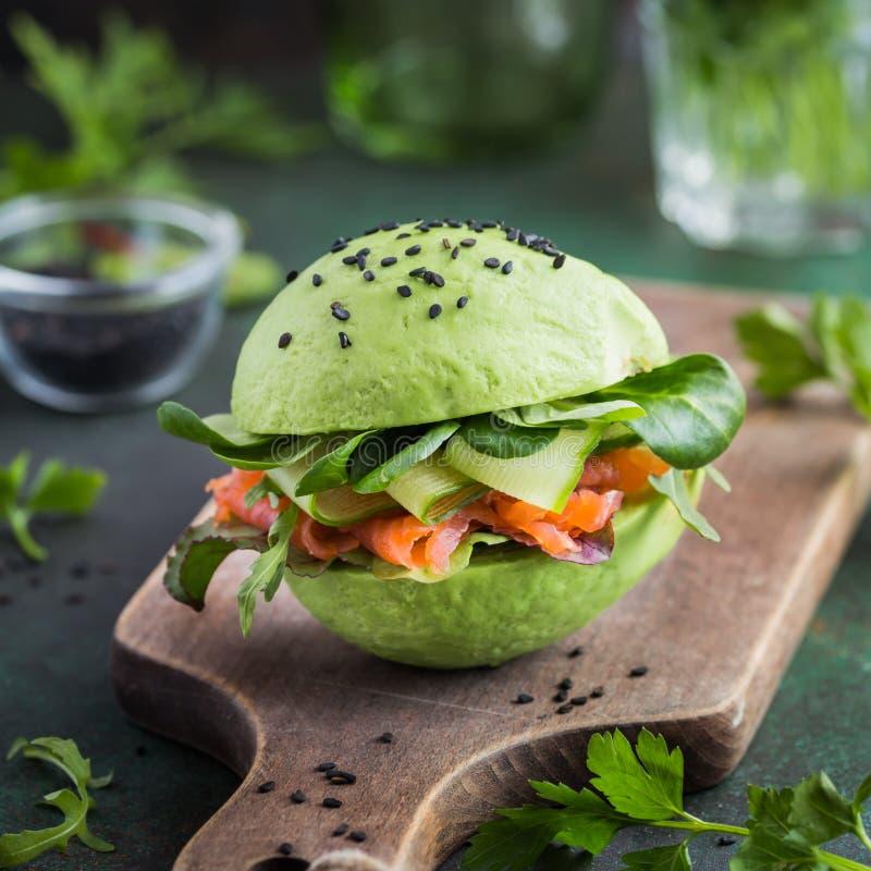与盐味的三文鱼和新鲜蔬菜的鲕梨汉堡 免版税库存照片