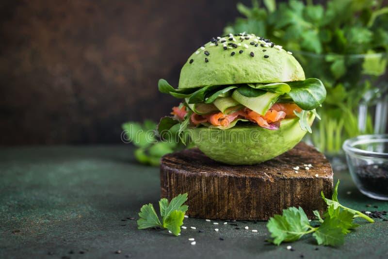 与盐味的三文鱼和新vegetabl的健康未加工的鲕梨汉堡 免版税库存图片