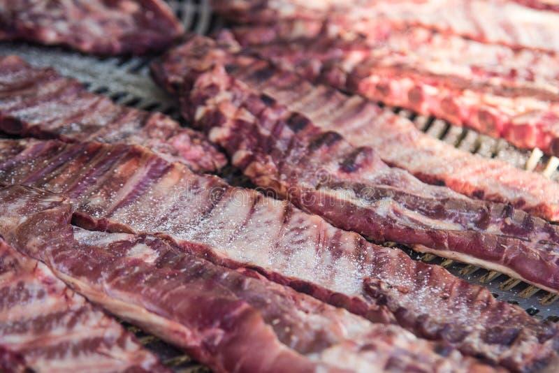 与盐和胡椒的新鲜的生肉肋骨在大金属格栅 选择聚焦 3 免版税库存照片