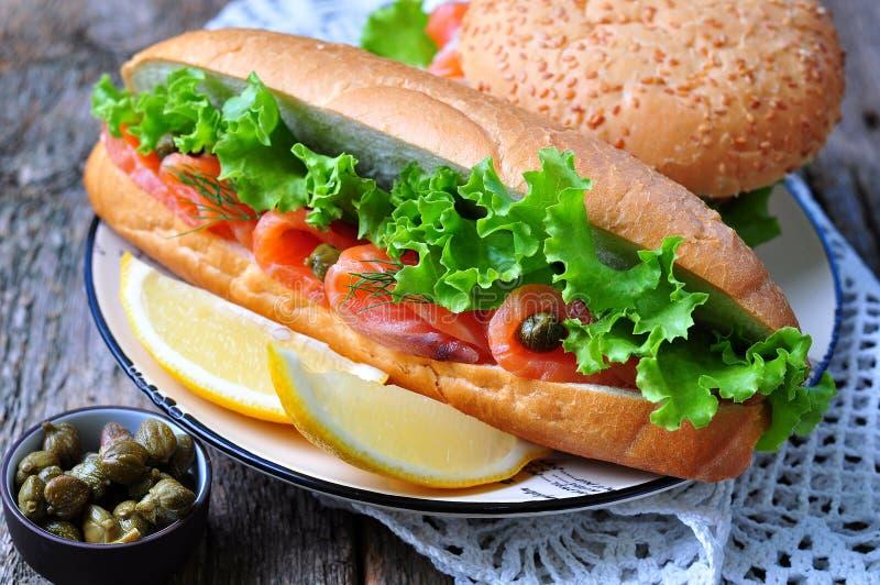 与盐渍的三文鱼、莴苣、白洋葱和雀跃的三明治 免版税库存照片