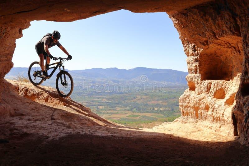 与盔甲的被隔绝的下降在往一个洞的入口的一个登山车的车手和背包在夏天 库存图片