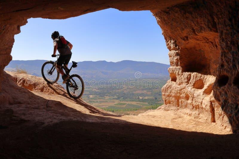 与盔甲的车手和背包在留给洞的夏天在登山车努力 库存图片