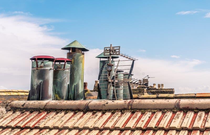 与盖帽的老金属烟囱通气管弄脏与创造象出现的年龄一个雕塑在一个老电视天线旁边 免版税图库摄影