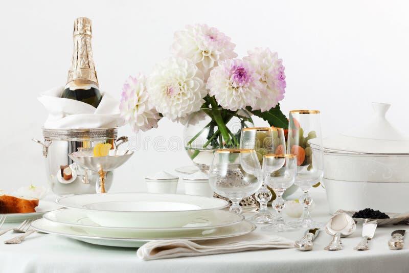 与盘和香槟的桌 免版税库存图片