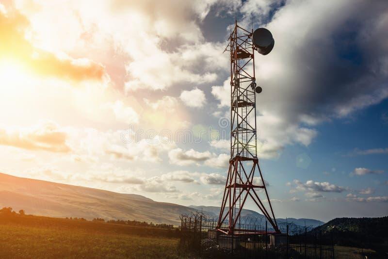 与盘的电信塔和在山的流动天线在日落天空背景 库存照片