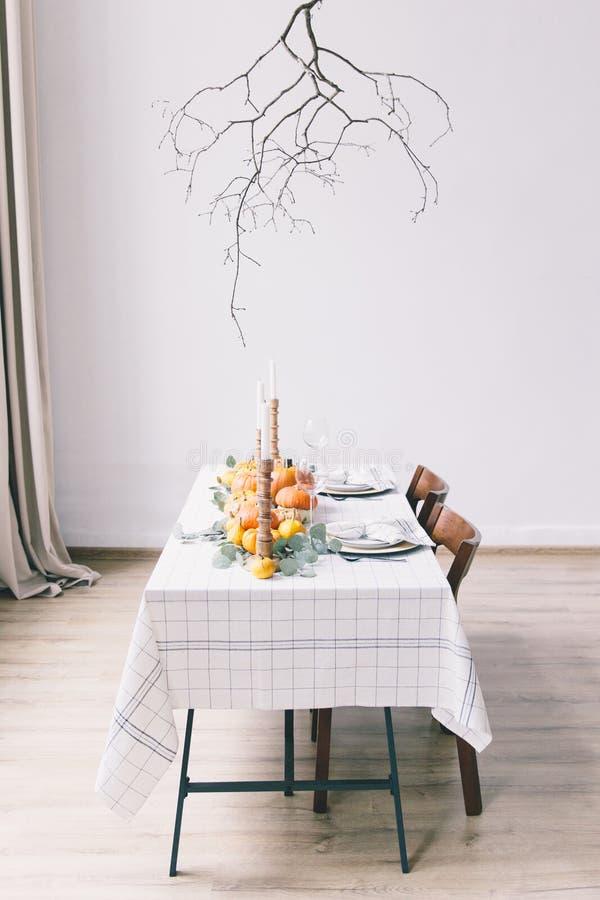 与盘的白色桌和食物在屋子里 黄色南瓜 免版税库存照片