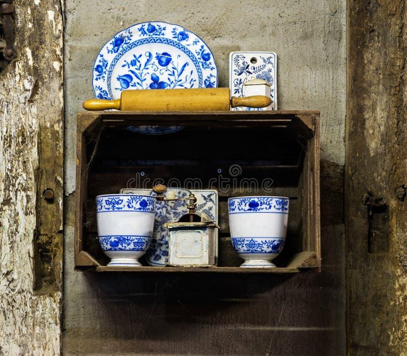 与盘的老磨咖啡器在墙壁上的碗柜 库存图片
