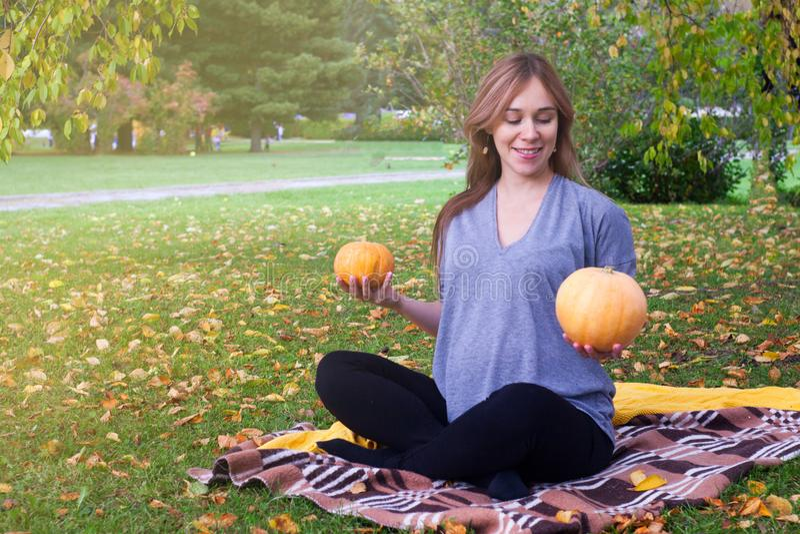 与盘的腿坐草草坪和看她的有柔和的微笑的愉快的年轻怀孕的模型画象腹部 远期 免版税库存照片