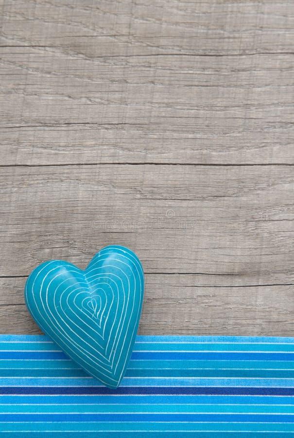 与相称被雕刻的线的蓝色心脏在灰色木背景 免版税库存照片