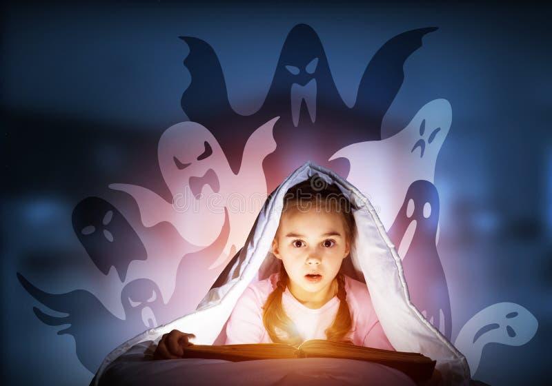 与看书的害怕的孩子在毯子下 图库摄影
