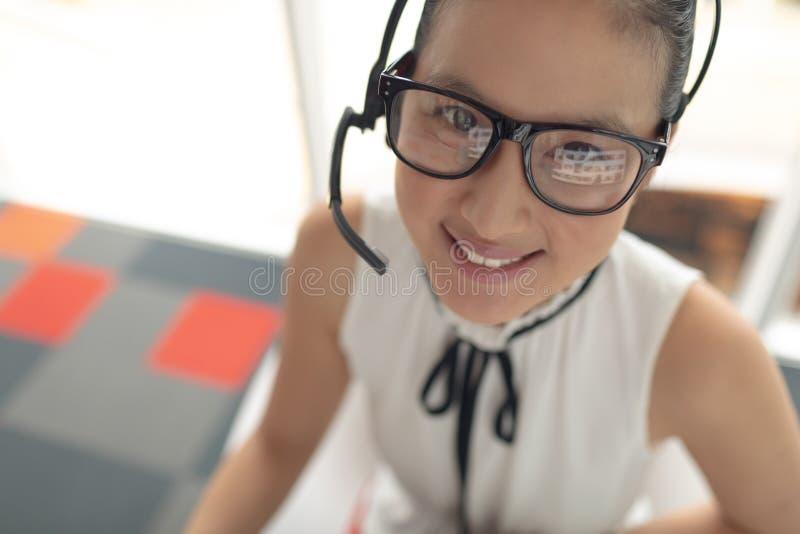 与看照相机的耳机的女性客服执行委员在一个现代办公室 免版税库存图片
