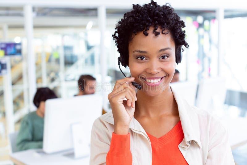 与看照相机的耳机的女性客服执行委员在办公室 免版税库存照片