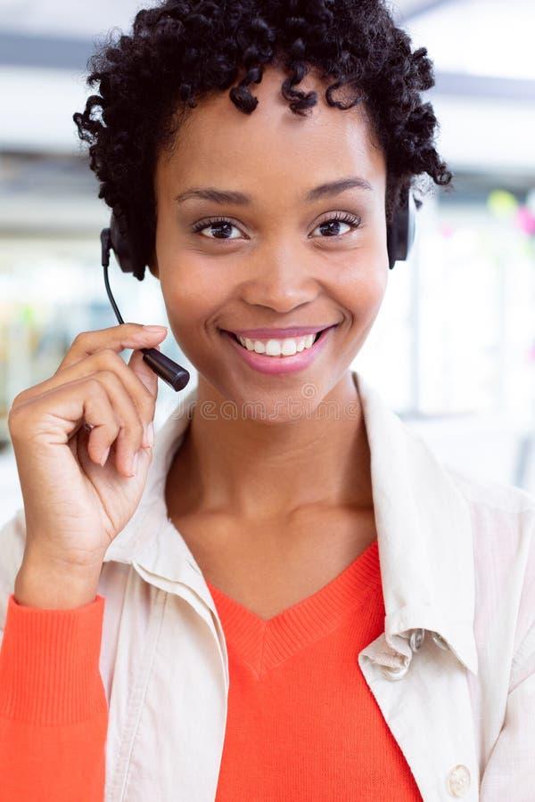 与看照相机的耳机的女性客服执行委员在办公室 图库摄影