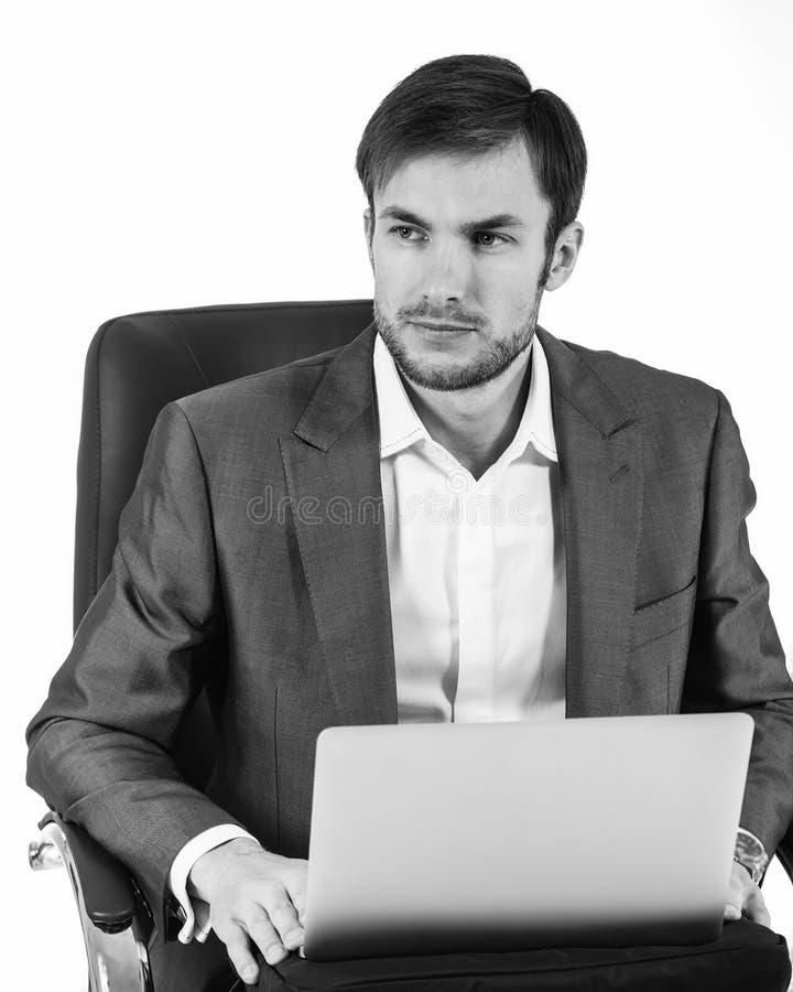 与看的膝上型计算机的商人  轻的背景 免版税库存照片