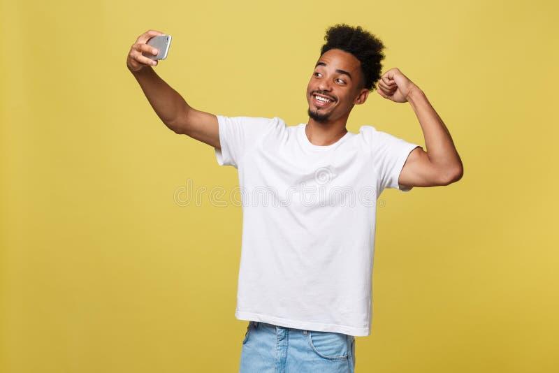 与看起来激动的有的手机的年轻美国黑人的黑人微笑的愉快的采取的selfie自画象图片 免版税库存照片