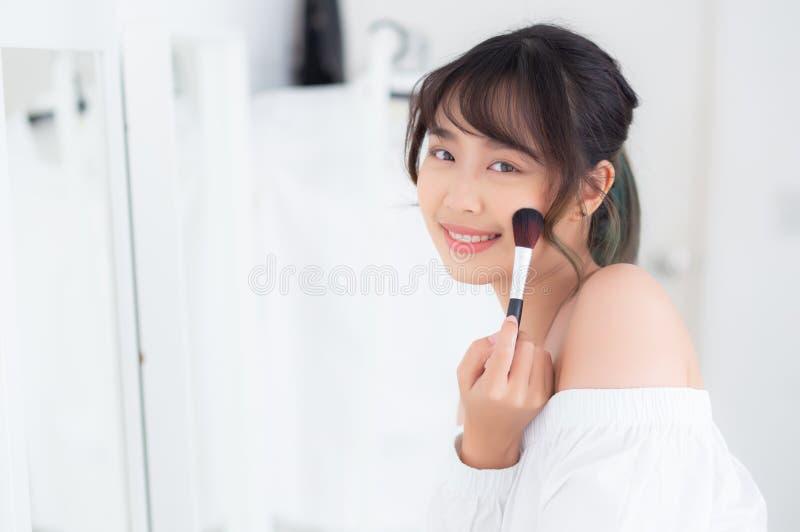 与看镜子的面孔的秀丽画象年轻亚洲妇女微笑申请与面颊刷子的构成在卧室 免版税库存图片