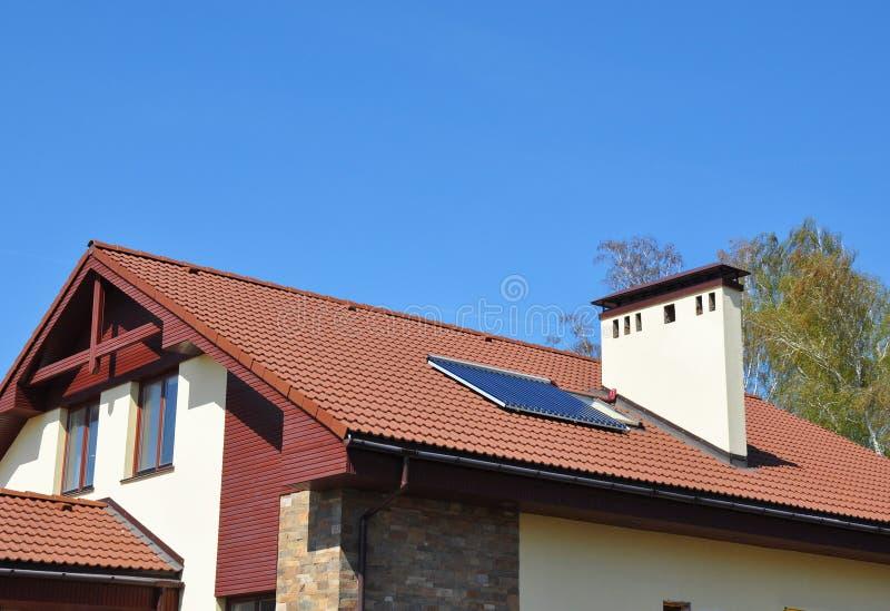 与真空太阳水嵌入式供暖器,太阳电池板,室外的天窗的舒适房子屋顶 库存图片
