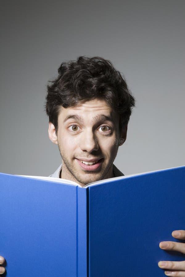 与眼睛大开举行的书的吃惊的年轻男性 库存图片
