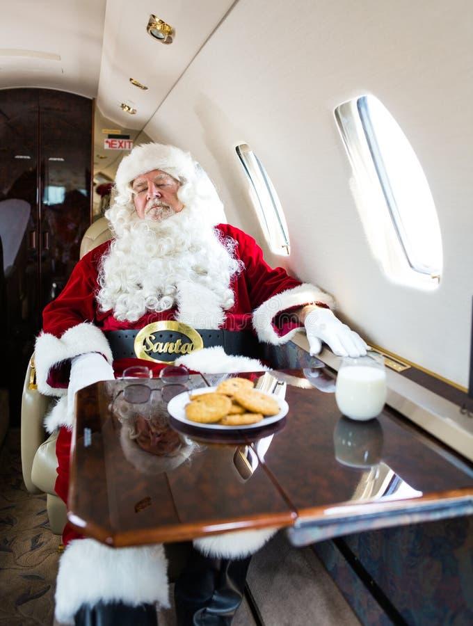 与眼睛的圣诞老人结束了放松在私人喷气式飞机 免版税库存照片