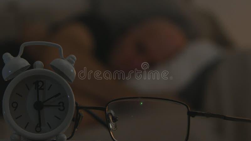 与睡觉在沙发的一个人的时钟和镜片图象在被弄脏的背景中 库存照片