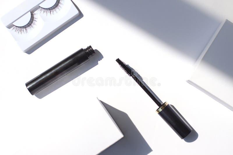 与睫毛卷发的人和假睫毛的黑染睫毛油框架在明亮的白色背景 化妆被隔绝的产品 库存图片